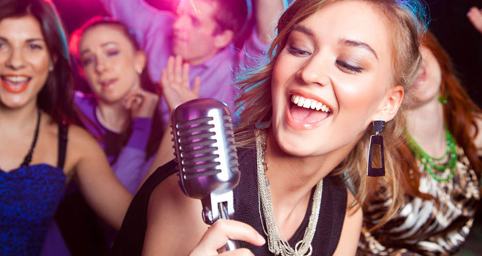 Girl singing karaoke with friends and professional lighting